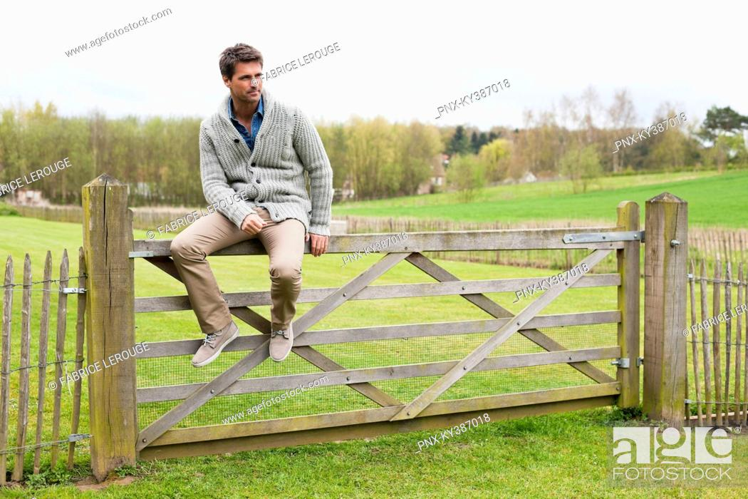 Stock Photo: Man sitting on the gate of a cottage.
