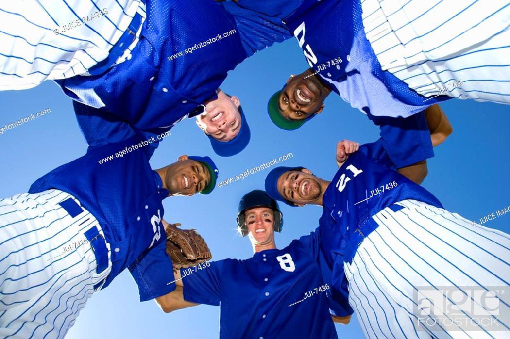 Stock Photo: Baseball team, in blue uniform, standing in huddle, smiling, portrait, upward view.