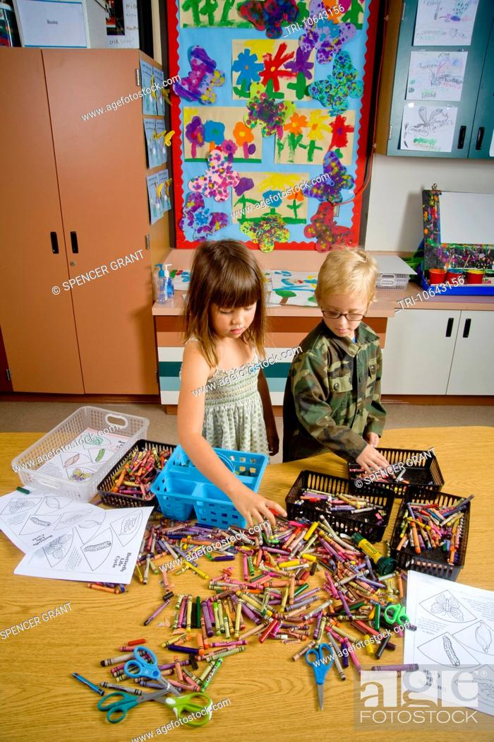 Photo de stock: Kindergarten children in San Clemente, CA, collect and organize a table full of classroom objects including crayons and worksheets.
