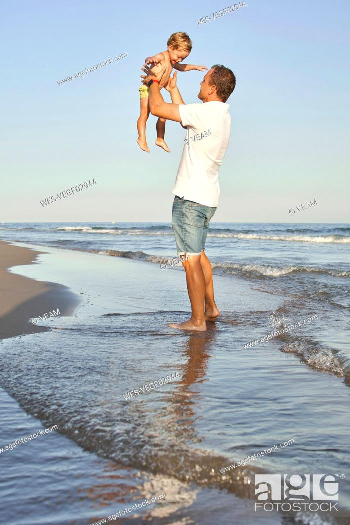 Stock Photo: Man picking up son while standing at beach.