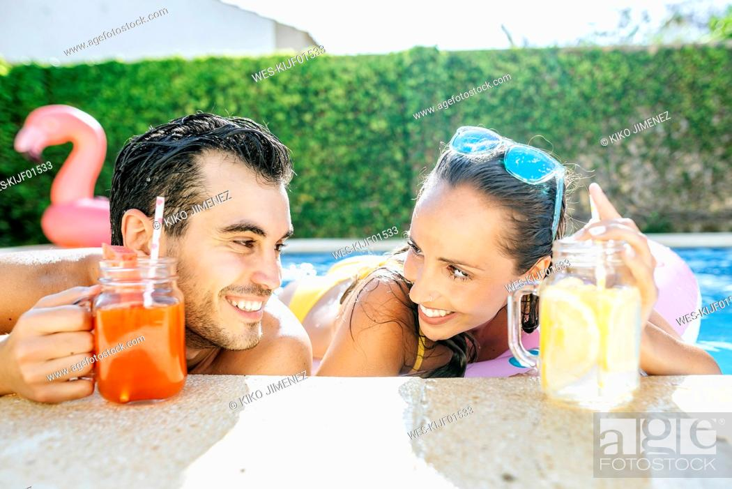 Photo de stock: Happy couple in swimming pool with drinks at the poolside.