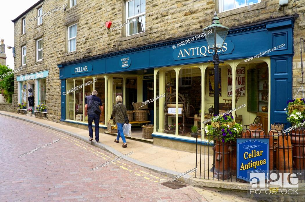 Stock Photo: Tourists walking past antiques shop in the Main Street. Hawes, Wensleydale, Yorkshire Dales National Park, Yorkshire, England, United Kingdom, Europe.