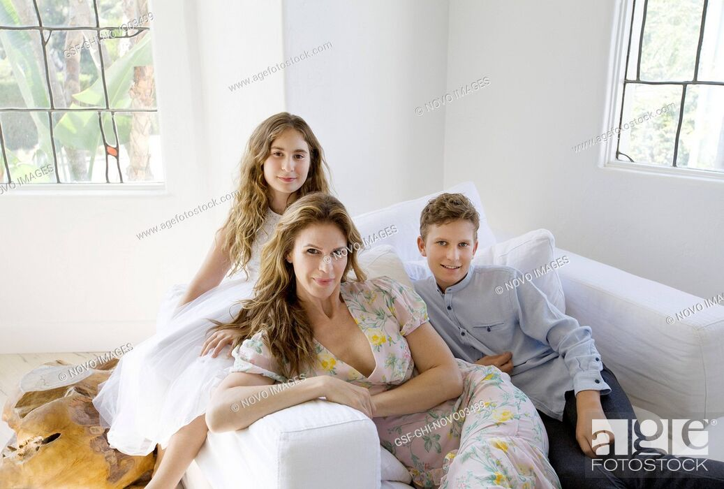 Imagen: Portrait of Mother and her Two Children Sitting on Upholstered Chair.