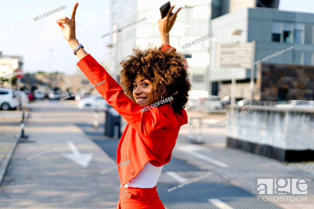 Stock Photo: Portrait of happy young woman wearing fashionable red pantsuit showing victory sign.