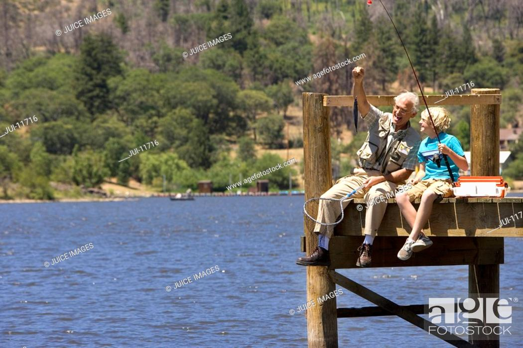 Stock Photo: Grandfather and grandson 10-12 fishing on jetty, low angle view.