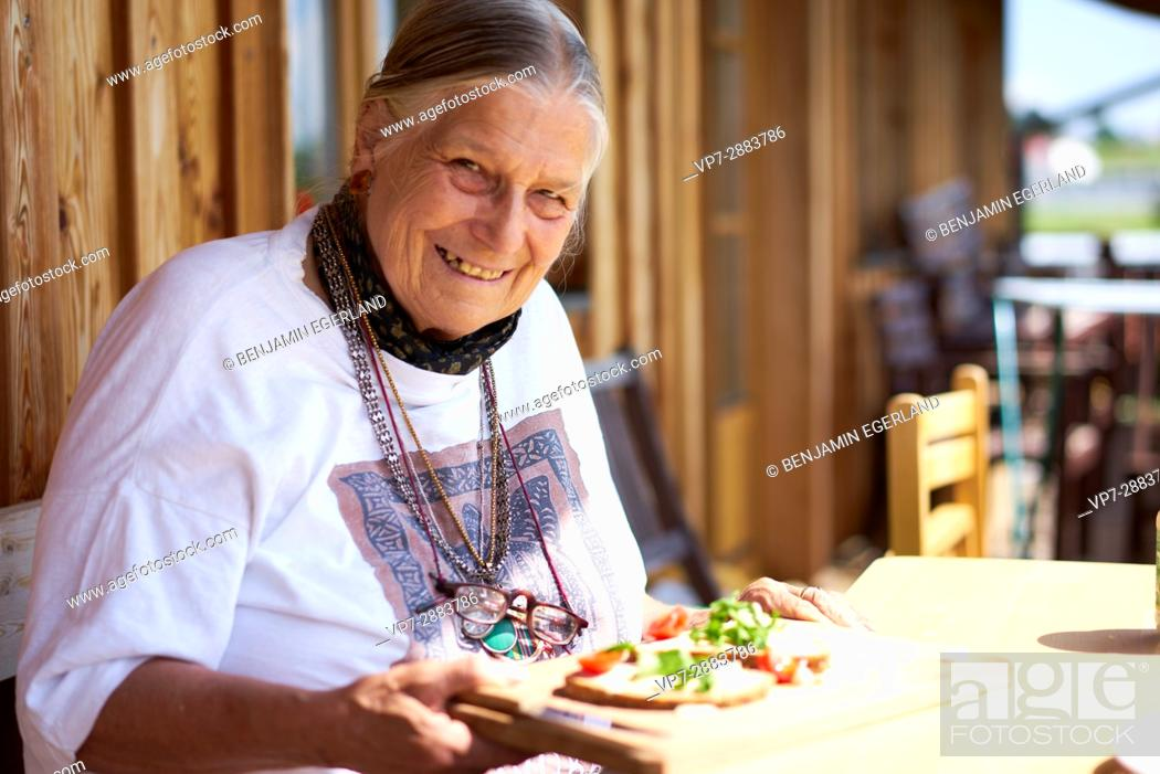 Stock Photo: happy senior woman eating healthy bread with vegetables.