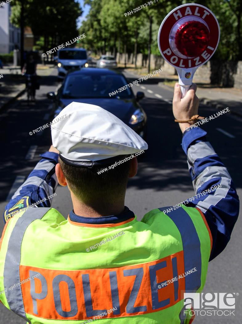 Stock Photo: 13 July 2020, Saxony, Dresden: A motorcycle policeman waves a police trowel to the side of a motorist during a police check.