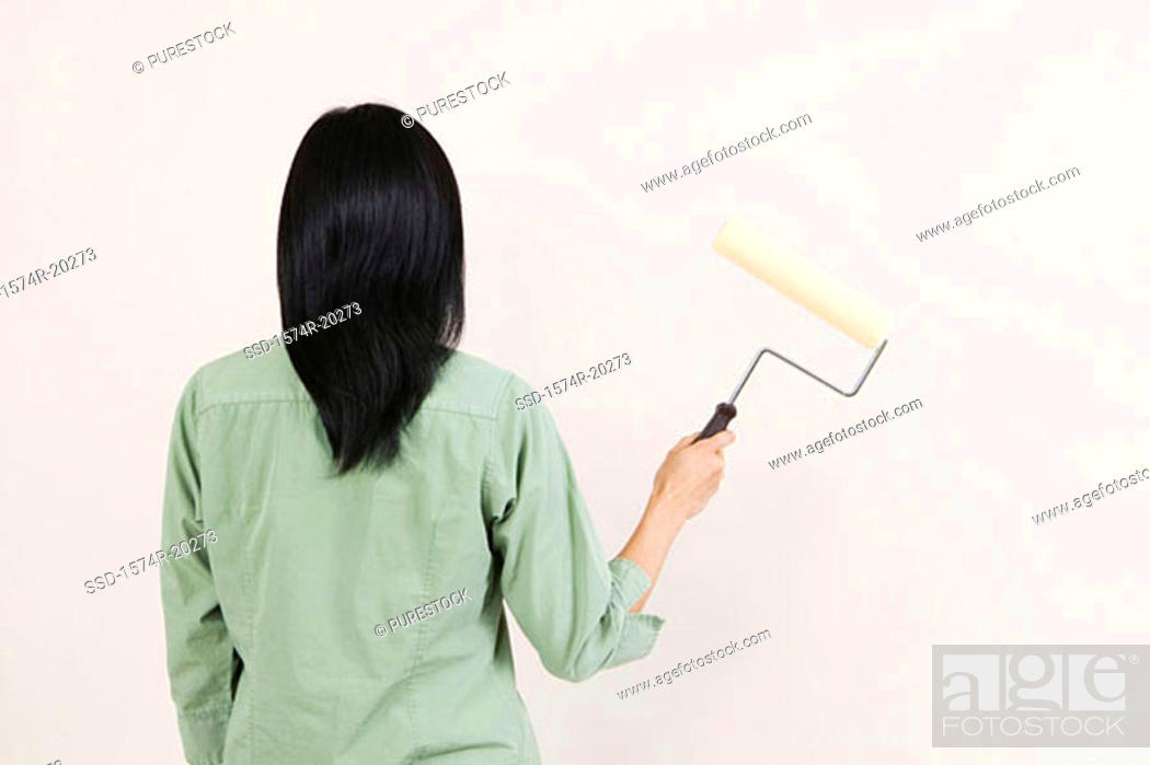 Stock Photo: Rear view of a woman holding a paint roller.