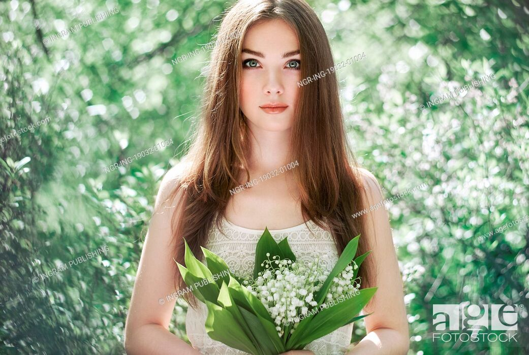 Stock Photo: Portrait of beautiful young woman with lily of the valley. Girl on nature. Spring flowers. Fashion beauty.