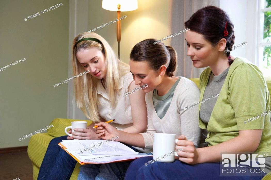 Stock Photo: Three young women sitting on couch.