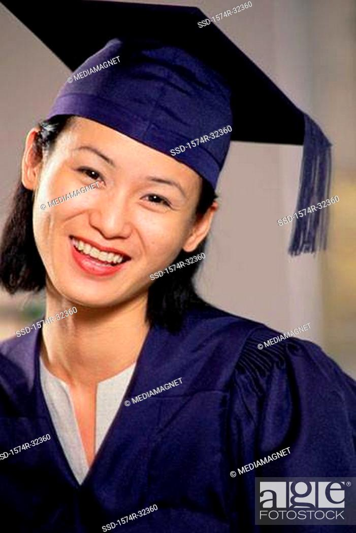 Portrait of a young woman wearing a graduation gown smiling, Stock ...