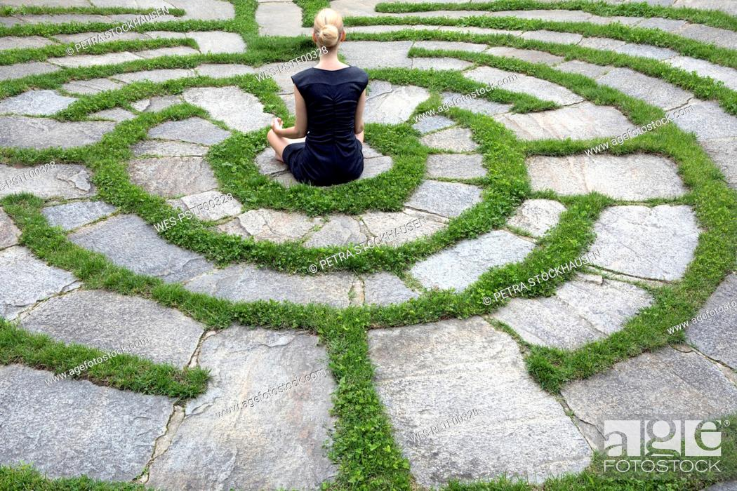 Imagen: Italy, Alto Adige, Lana, woman sitting in natural open air maze meditating.