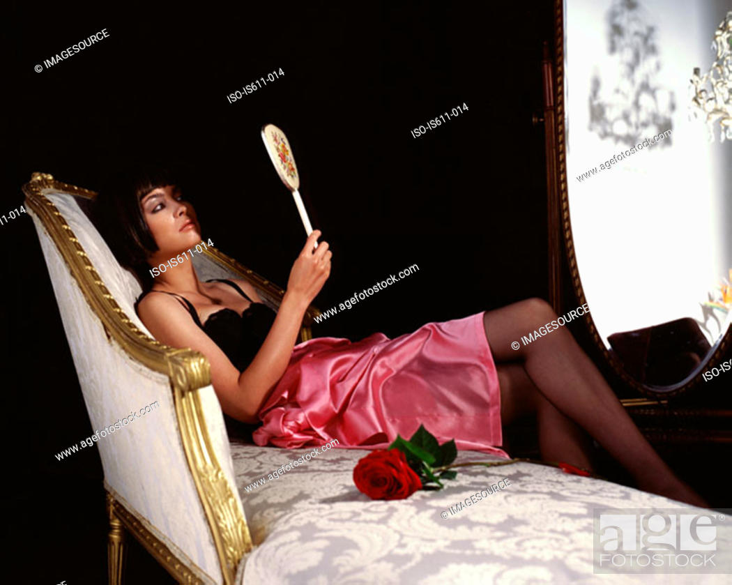 Stock Photo: Young woman looking at herself in a hand mirror.