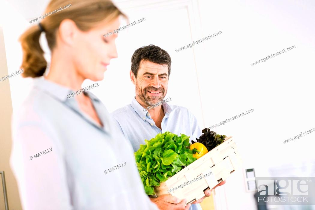 Stock Photo: Mature couple preparing box of fresh vegetables in kitchen.