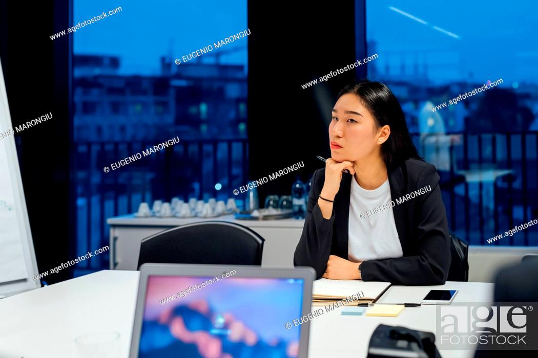 Stock Photo: Businesswoman listening at conference table meeting.