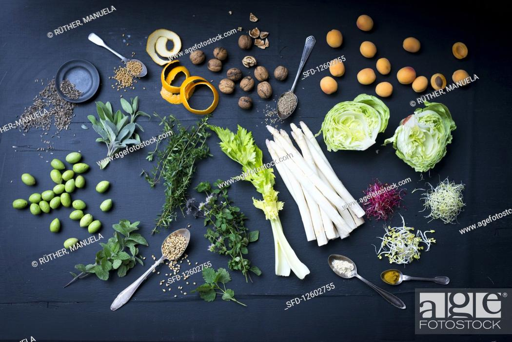 Stock Photo: Still life with vegetables, salad, herbs, sprouts, apricots and nuts.