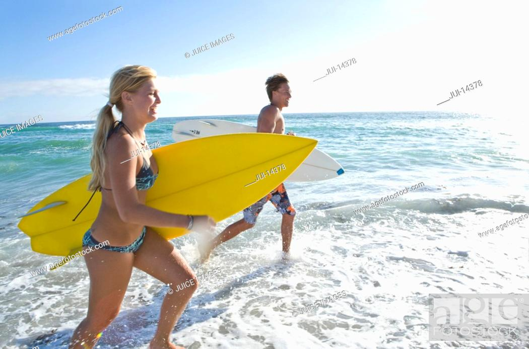Stock Photo: Young couple with surfboards in sea, side view.