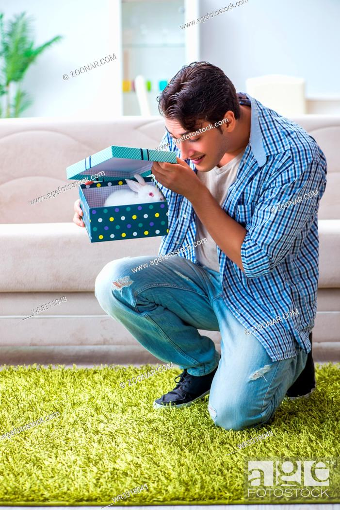 Stock Photo: Young man getting rabbit as birthday present.