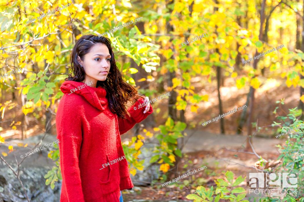 Stock Photo: A 19 year old brunette woman walking on a path in a forest in the autumn.