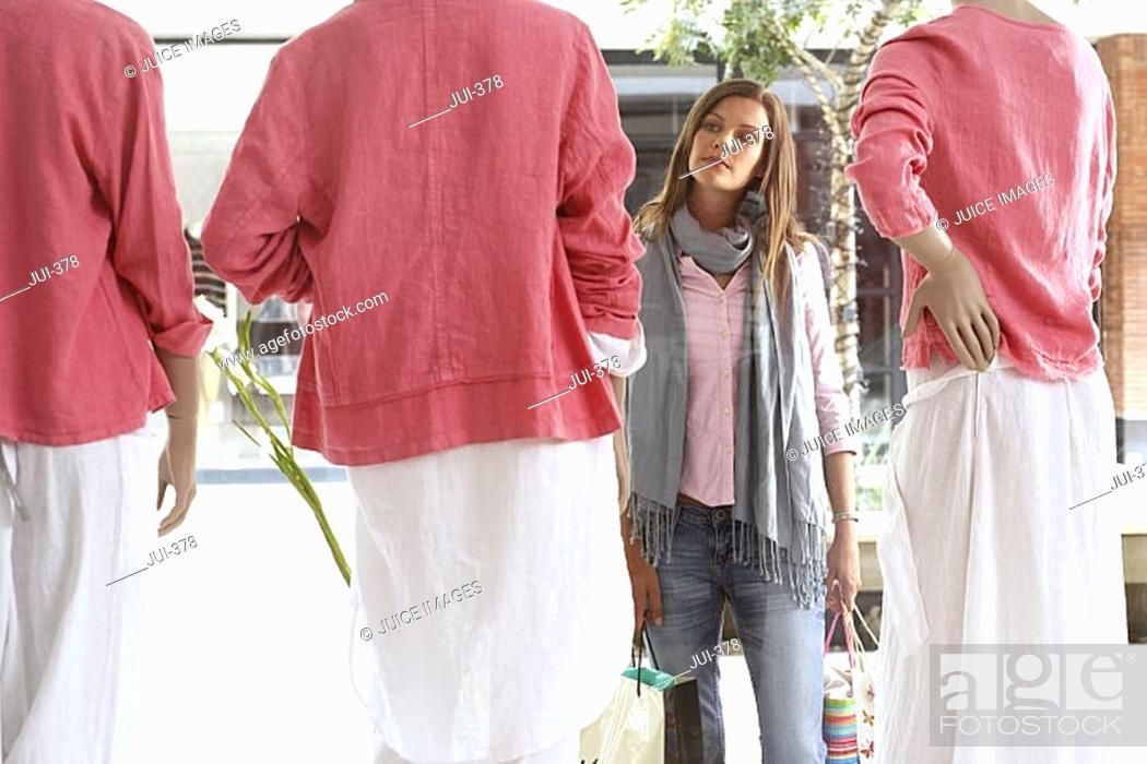 Stock Photo: Woman window shopping, looking at three mannequins wearing pink tops and white skirts in clothes shop.