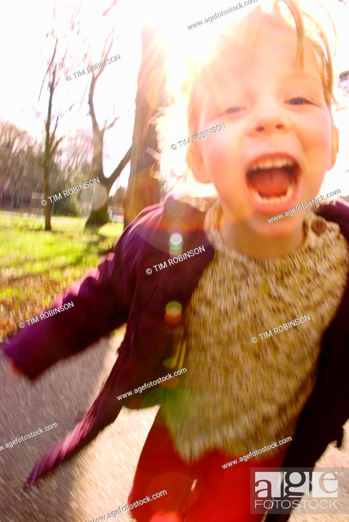 Stock Photo: 6 year girl running towards camera in park with happy expression.