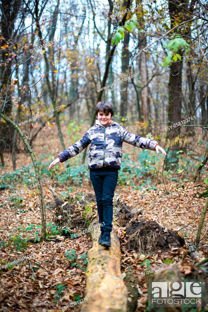 Imagen: smiling child walks on fallen tree in balance.
