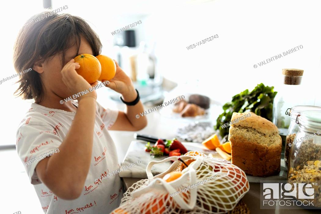 Stock Photo: Boy in kitchen covering eyes with oranges.