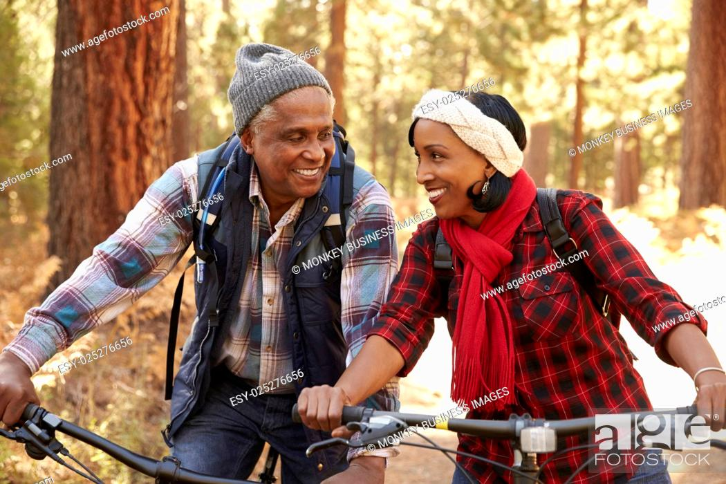 Stock Photo: Senior Couple Cycling Through Fall Woodland.
