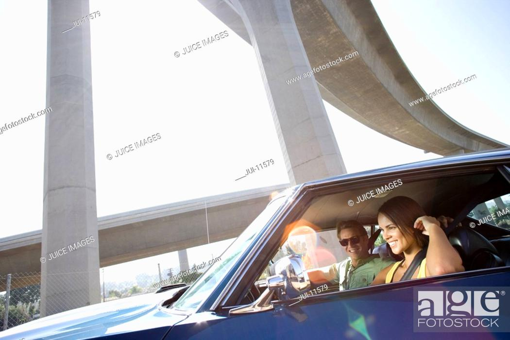 Stock Photo: Young couple in car by freeway overpass, smiling lens flare.