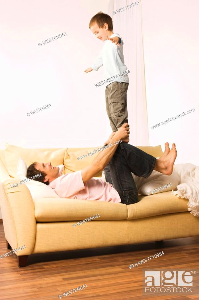 Stock Photo: Father and son 4-5, fooling about, boy balancng on man's knees.
