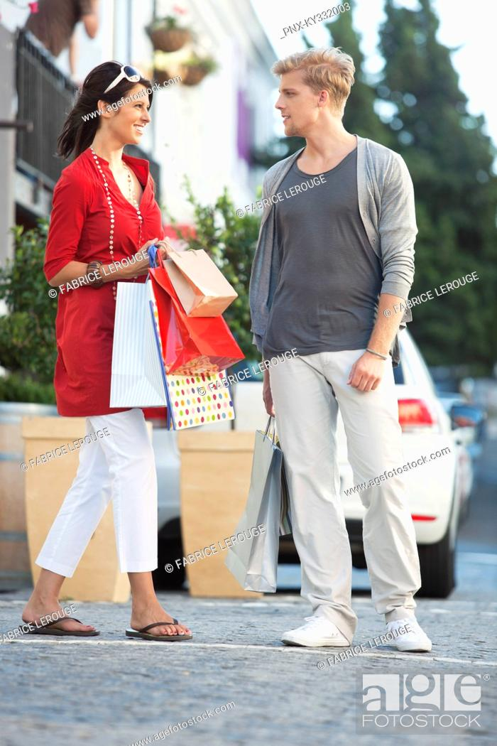 Stock Photo: Young couple looking at each other with shopping bags on a street.