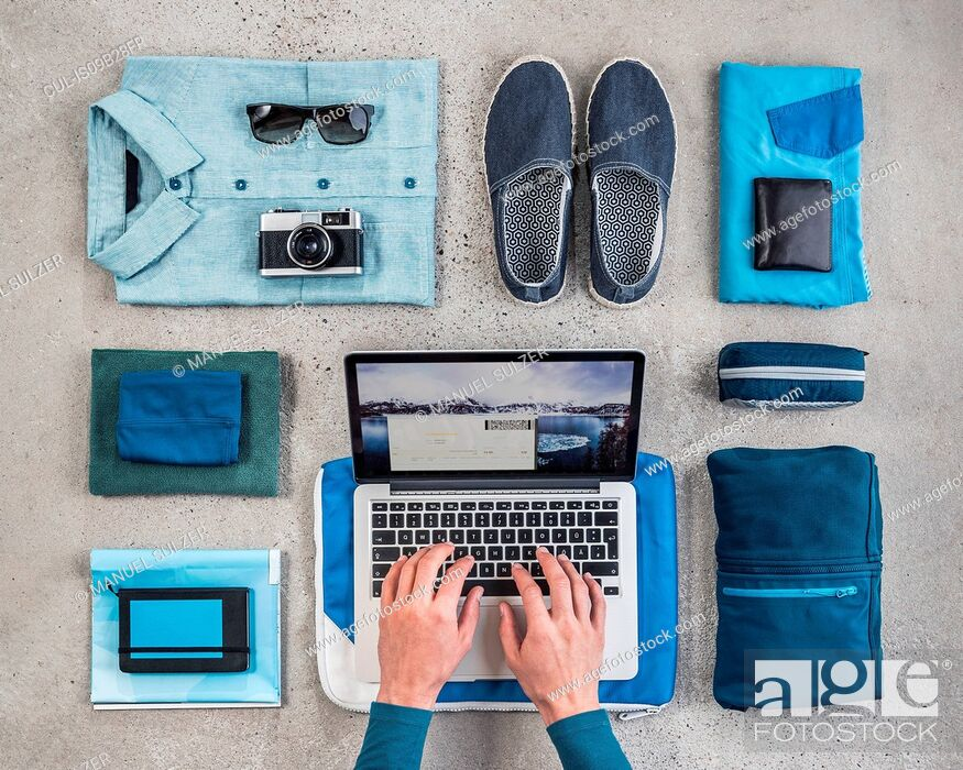 Imagen: Overhead view of man's hands typing on laptop surrounded by travel packing items, with blue shirt, retro camera, wash bag and notebook.