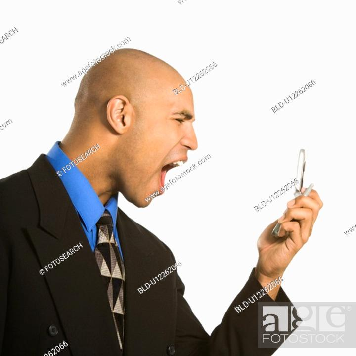 Stock Photo: Profile of angry businessman shouting into phone.