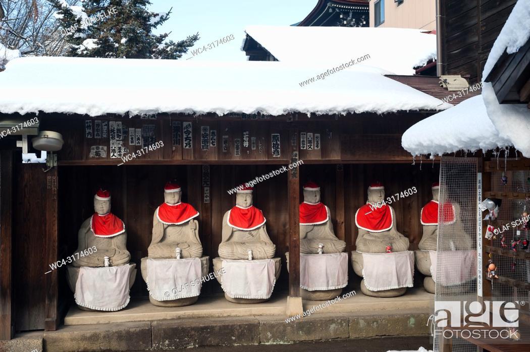 Stock Photo: Takayama, Gifu, Japan, Asia - A row of Jizo statues made of stone, wearing red hats and bibs is seen sitting under a wooden shelter at the Hida Kokubun-ji.