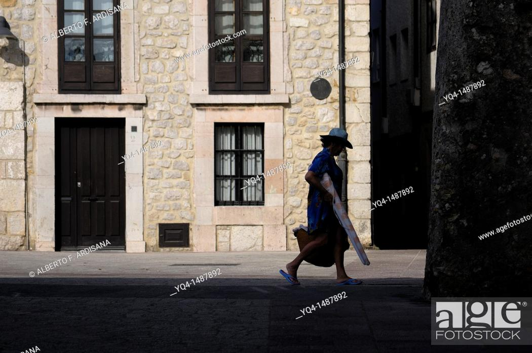 Stock Photo: Woman with bag and hat, walking the old town of Llanes, Asturias, Spain.