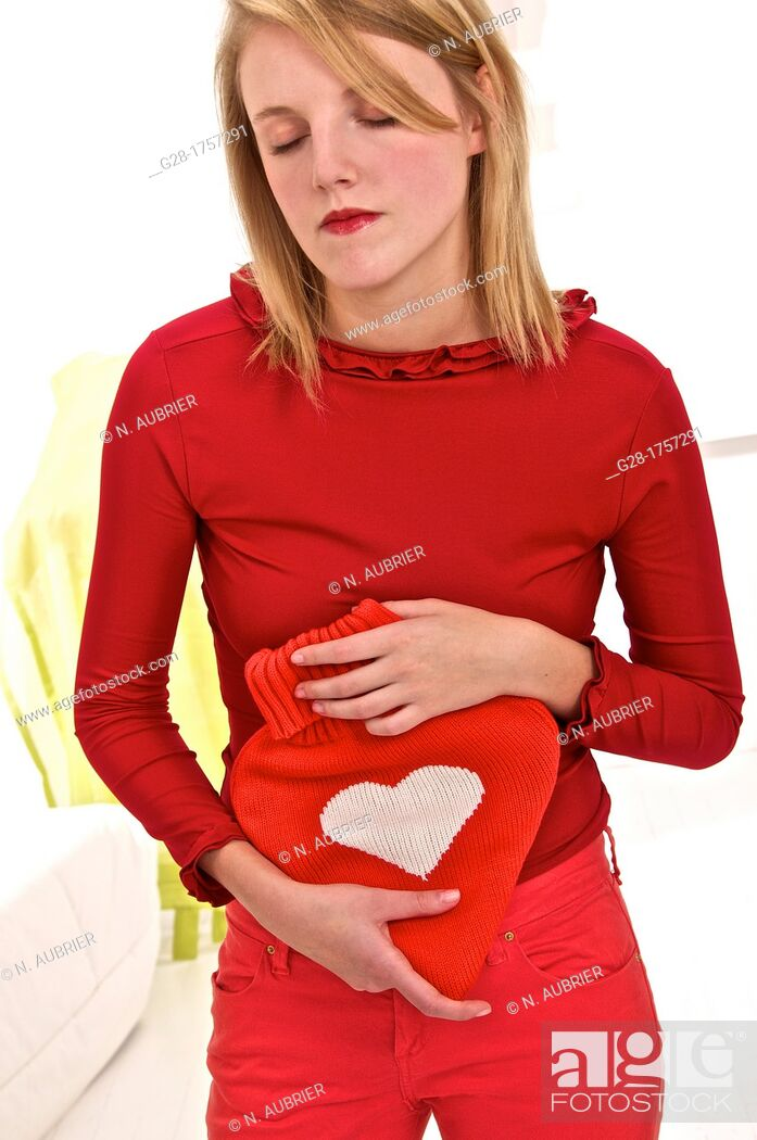 Stock Photo: Young blond woman holding a red heart shaped hot water bottle.