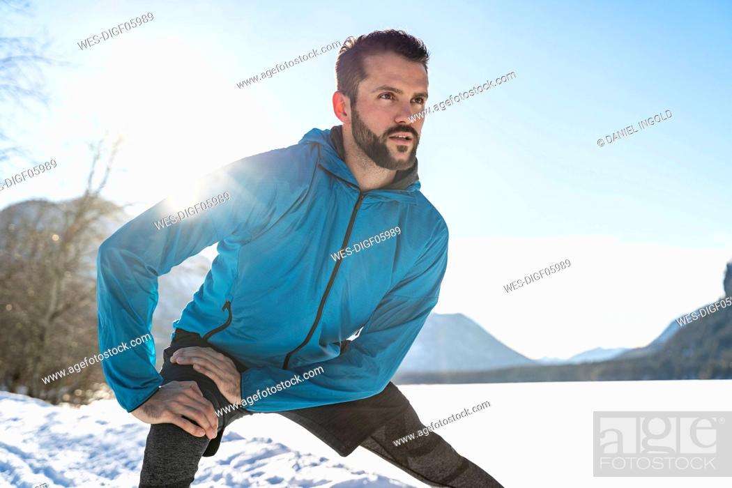 Photo de stock: Germany, Bavaria, sportive man stretching in winter.