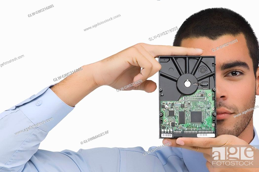 Stock Photo: Portrait of a businessman holding a hard drive in front of his face.