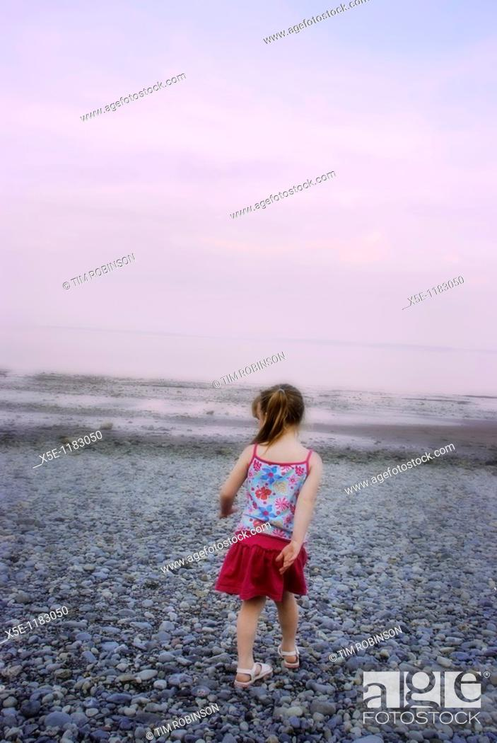 Stock Photo: Rearview 6 year girl walking away from camera on stony beach.