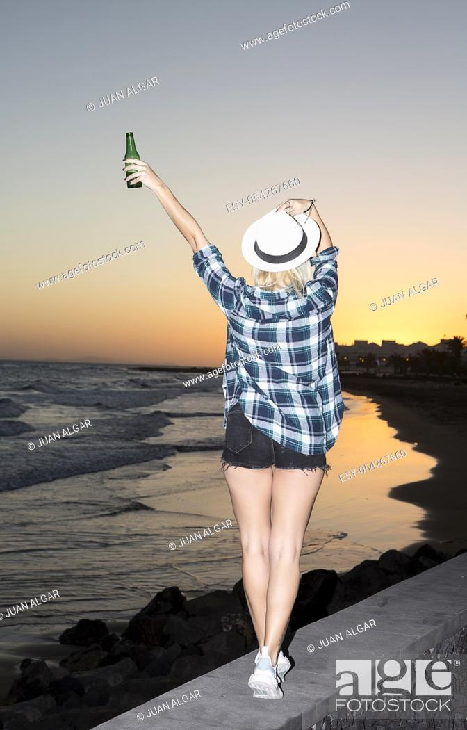 Stock Photo: Back view of pretty woman standing with bottle of beer at seaside. Lanzarote, Canary Islands, Spain.