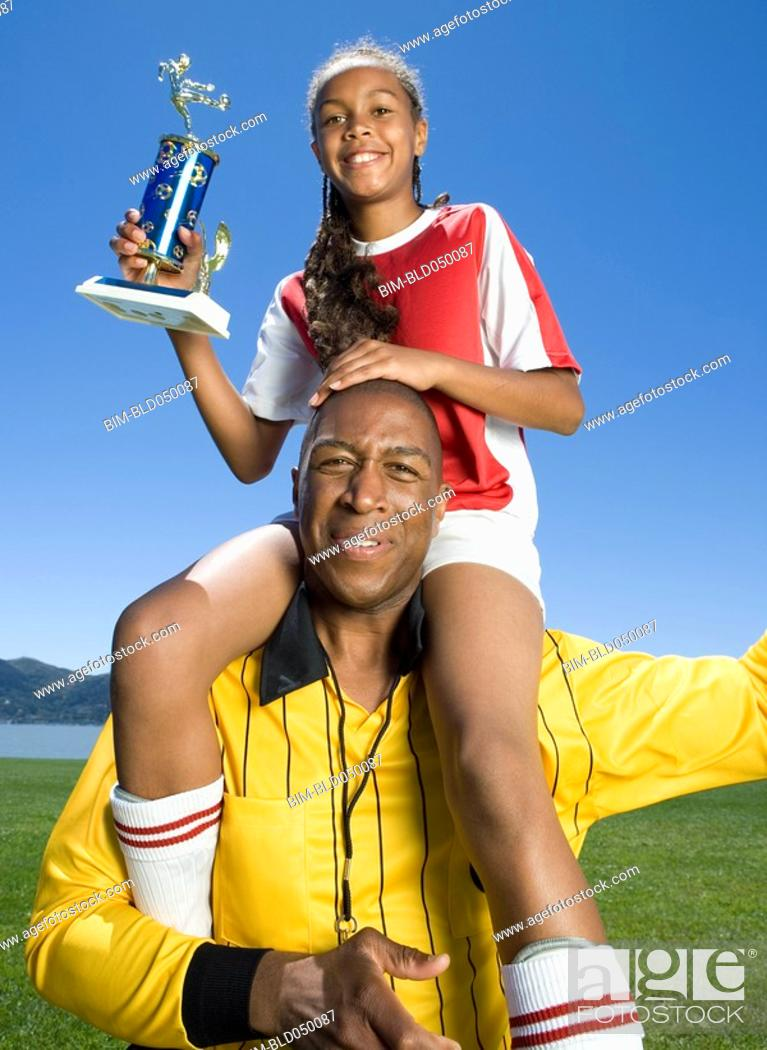 Stock Photo: Mixed Race girl on soccer coach's shoulders.