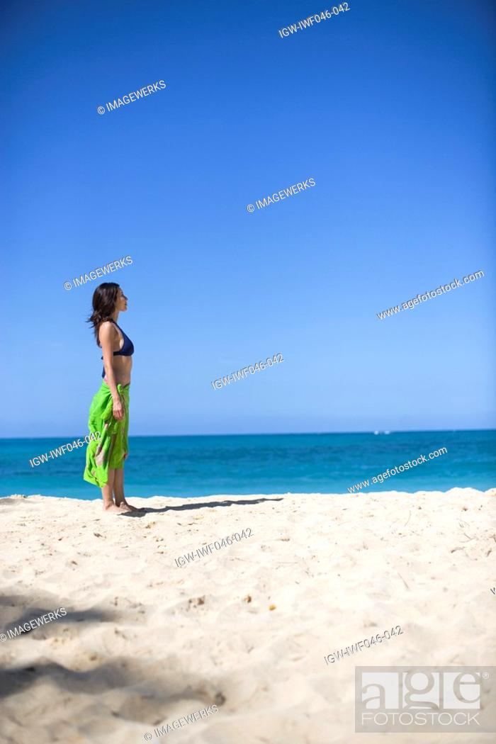 Stock Photo: Side view of a young woman standing on beach.