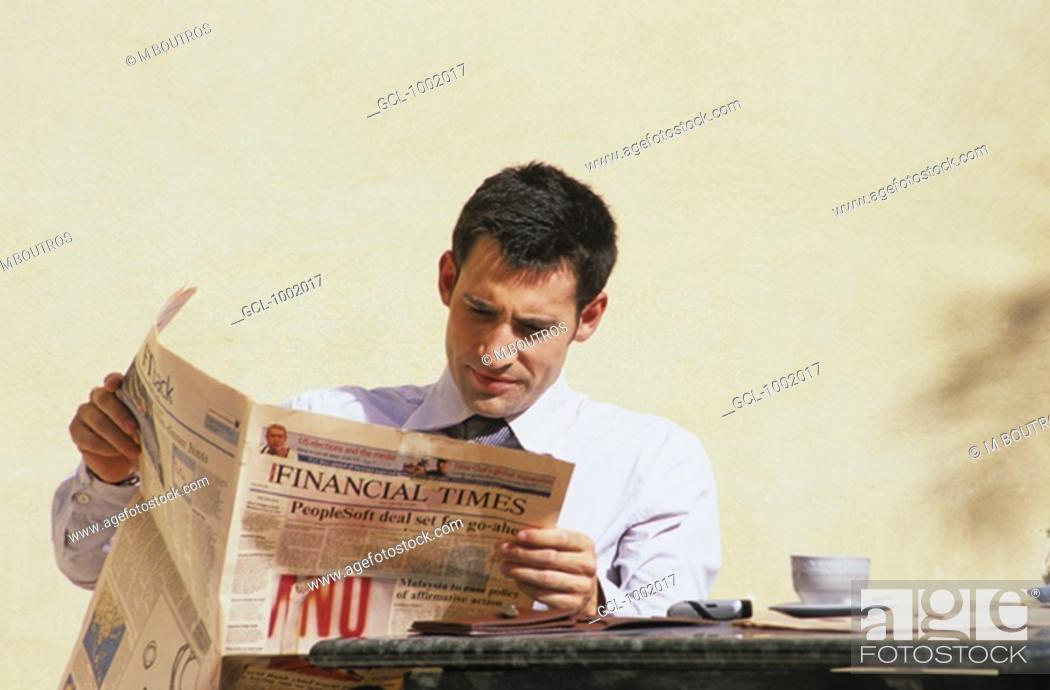 Stock Photo: Businessman reading newspaper during a coffee break.