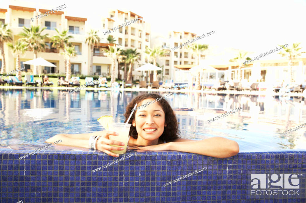 Stock Photo: Hispanic woman with drink leaning on pool edge.