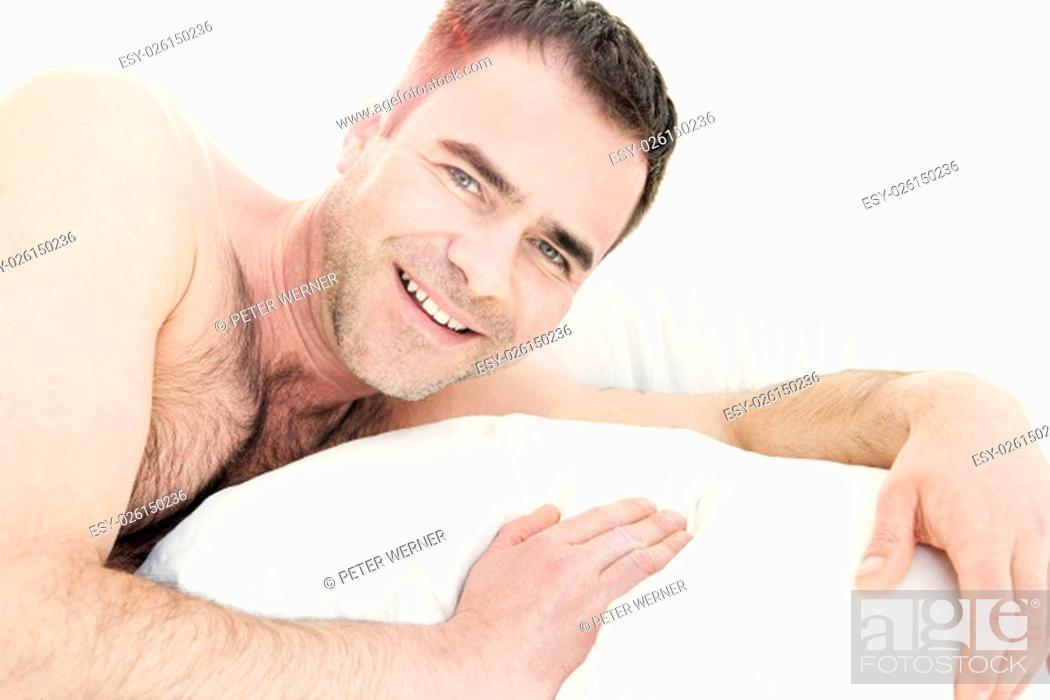 Stock Photo: shirtless man in bed and smiling at camera.