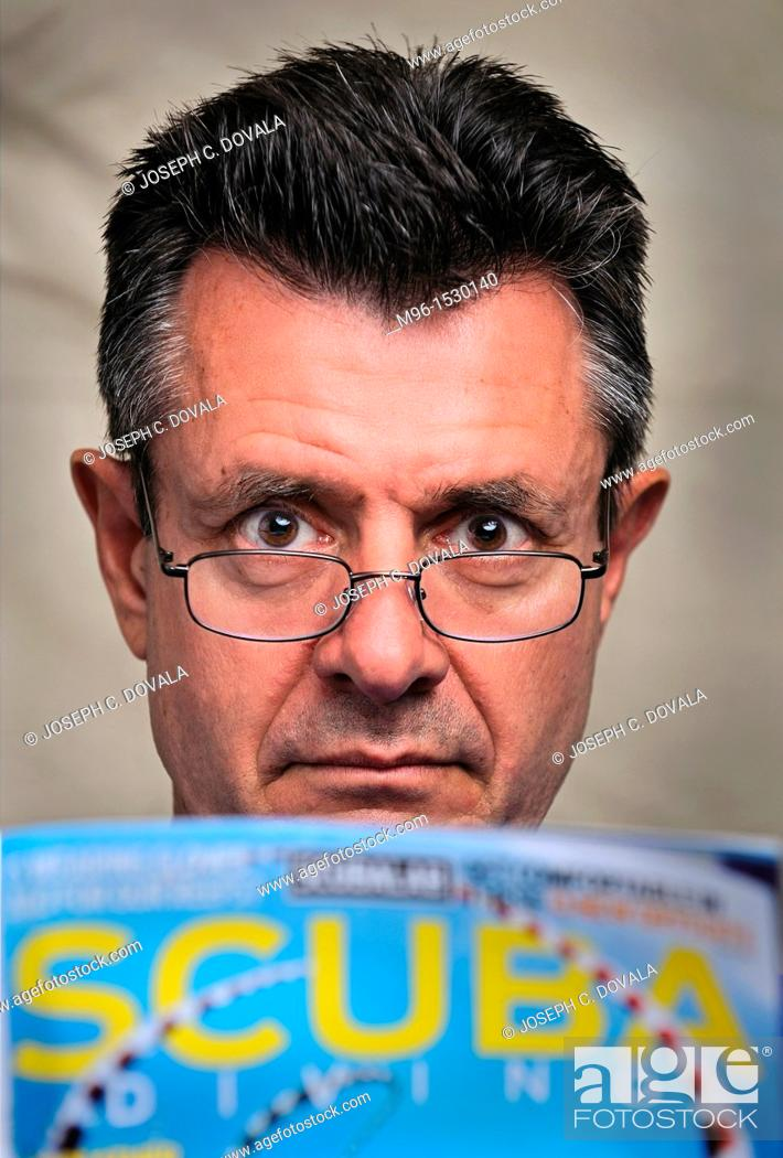Stock Photo: Middle aged man looking at scuba diving magazine close up, Thousand Oaks, California, USA.