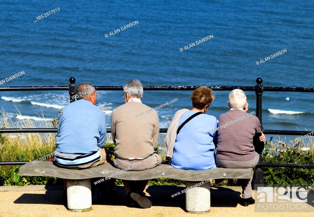 Stock Photo: Elderly couples sitting on seat overlooking sea at Saltburn by the Sea, North Yorkshire, England, United Kingdom.