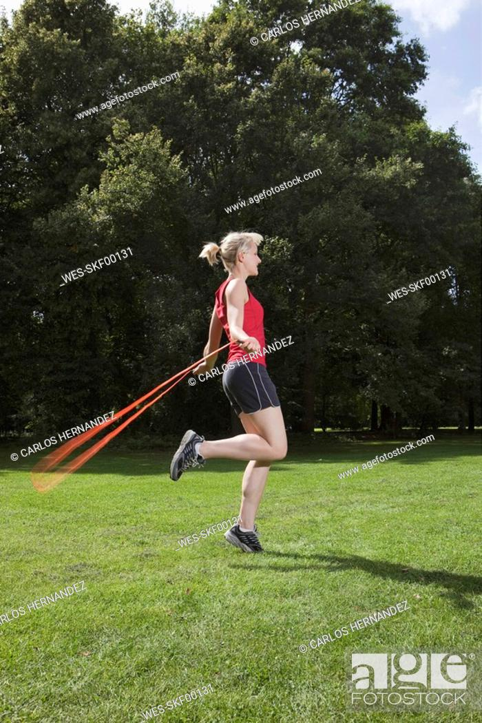 Stock Photo: Germany, Berlin, Young woman jumping rope in park.