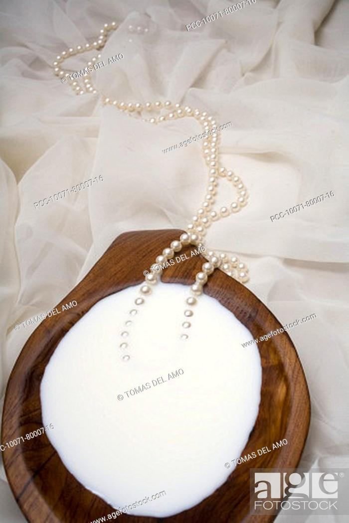 Stock Photo: Spa elements, koa bowl filled with milk, garnished with a pearl necklace.