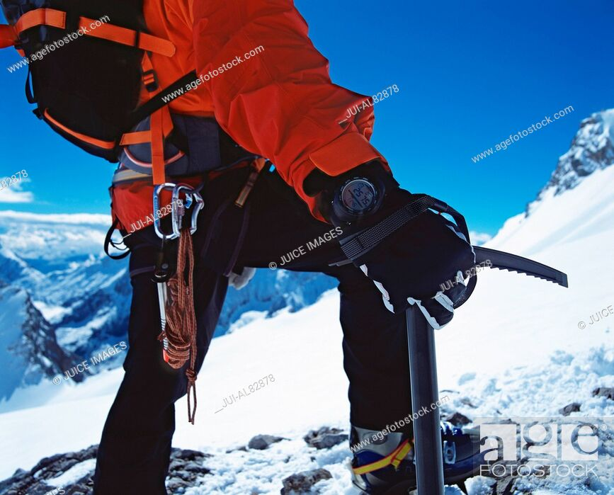 Stock Photo: Close up of hiker holding ice axe on snowy mountain.